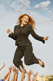 Happy successful business woman jumping. Over their hands up royalty free stock photo