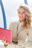Happy successful business woman in suit holding modern red laptop Stock Image