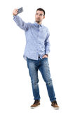 Happy successful businessman taking selfie looking at smart phone. Full body length portrait isolated over white background stock photo