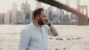 Happy successful European businessman makes a phone call on smartphone, talking and smiling near Brooklyn Bridge 4K.