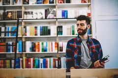 Free Happy Successful Hipster Guy Picking Literature And Making Research In Bookstore Royalty Free Stock Photo - 187102115