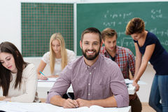 Happy successful male student. Happy successful young bearded male student sitting at his desk in a classroom with his fellow students giving the camera a Royalty Free Stock Photo