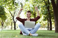 Happy successful man with arms raised in air. Young casual student with laptop celebrating victory outdoors, sitting on grass in park. Winner and achievement Stock Image