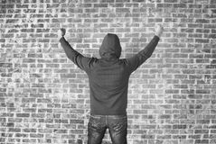 Happy and successful man. Young man covers his face with hands with bricks wall as background,black and white Royalty Free Stock Image