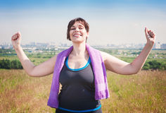 Happy successful plus size woman raising arms to the sky royalty free stock photography