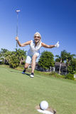 Happy Senior Woman Playing Golf & Putting. Happy successful senior woman playing golf putting a golf ball into a hole on a green and celebrating her success royalty free stock images