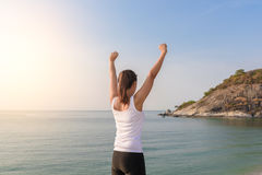 Happy successful sportswoman raising arms to the sky on golden b Royalty Free Stock Photography