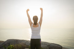 Happy successful sportswoman raising arms to the sky on golden b Stock Images