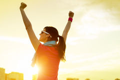 Sportswoman with arms up celebrating success Stock Image