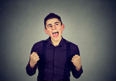 Happy successful student man winning fists pumped celebrating success Stock Images