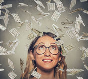 Happy successful woman in glasses looking up under a money rain Stock Photography