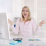 Happy successful young business woman with arms up at desk. Royalty Free Stock Images