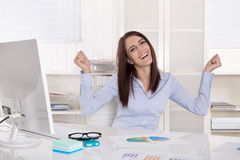Happy successful young business woman with arms up at desk. Stock Image