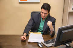 Happy successful young businessman, sitting at Royalty Free Stock Photo