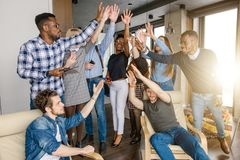 Happy successful young businessmen and women triumphing with raised hands. Happy successful young businessmen and women in casual clothes triumphing with raised Stock Photography