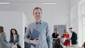 Happy successful young Caucasian businessman walking along modern light office smiling at camera slow motion RED EPIC. stock footage