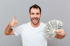 Happy successful young man holding money and showing thumbs up Stock Image