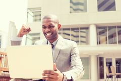 Happy successful young man with laptop computer celebrates success Royalty Free Stock Image