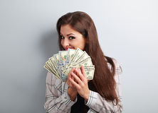 Happy successful young pretty woman holding dollars in hands and Royalty Free Stock Photos