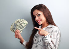 Happy successful young pretty woman showing the finger on dollar Stock Photo