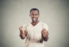 Happy successful young student man winning, fists pumped Stock Images