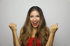 Happy successful young woman with raised hands shouting and celebrating success over gray background royalty free stock images