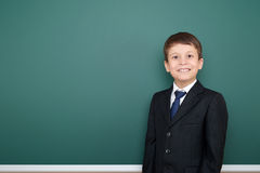 Happy successfull school boy in black suit portrait on green chalkboard background, education concept Stock Photo
