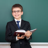 Happy successfull school boy with book portrait, dressed in classic black suit, on green chalkboard background, education and busi Stock Photography