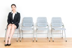 Happy suit woman sitting on company seat. Beautiful happy suit woman sitting on company seat in white background with wood floor and face to camera ready for royalty free stock images