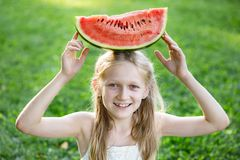 Girl eating watermelon. Happy summer - beautiful blond little girl eating watermelon on a green lawn stock photo