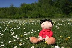 Happy summer doll. Happy doll enjoying the summer sunshine and cherishing a flower Stock Image