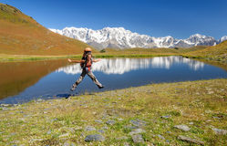 Happy summer girl jumping with backpack. Stock Image