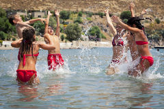 Happy summer holidays. Kids and mother enjoying themselves  jumping in the sea Stock Photo