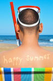 Happy summer. A man wearing a diving mask and a snorkel seated in a deckchair on the beach with the text happy summer written in his back as a tan mark stock image