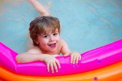 Happy summer pool. Good mood. Water for kids game. The child swims in the pool. Rest in a sea hotel. Home entertainment royalty free stock image