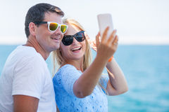 Happy summer selfie of young couple in sunglasses stock photography