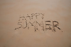 Happy summer text in sand beach Royalty Free Stock Photos