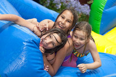 Happy summer. Three girls in inflatable swimming pool royalty free stock photo