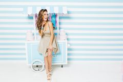 Happy summer time of pretty fashionable model in dress having fun on striped background. Sweet dessert truck, cakes