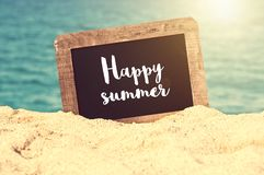 Happy summer written on a vintage chalkboard in the sand royalty free stock photography