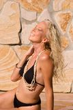 Happy Sun Bather. Passive outdoor posed attractive girl in a black bikini, make up, and jewelry Royalty Free Stock Photo