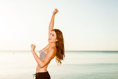Happy sunrise woman. Happy sunshine woman. Girl smiling  at sunrise on beach. Happy girl jumping on the beach on the sunrise time Royalty Free Stock Photo