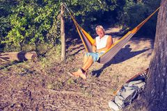 Happy sup surfer relaxes in a river camp. In hammock and having fun Stock Photography