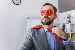 happy super businessman in mask and cape looking away stock photography