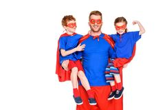 Happy super father holding smiling kids in masks and cloaks. Isolated on white royalty free stock photos