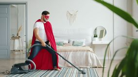Happy superman vacuuming floor at home then dancing holding vacuum cleaner