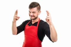 Happy supermarket employer holding double fingers crossed Stock Photography