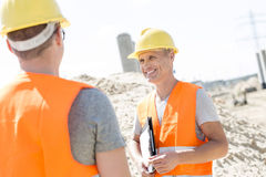 Happy supervisor discussing with colleague at construction site Stock Image