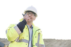 Happy supervisor using walkie-talkie at construction site against clear sky Royalty Free Stock Images