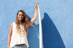 Happy surfer girl with surfboard in front of blue wall Stock Image